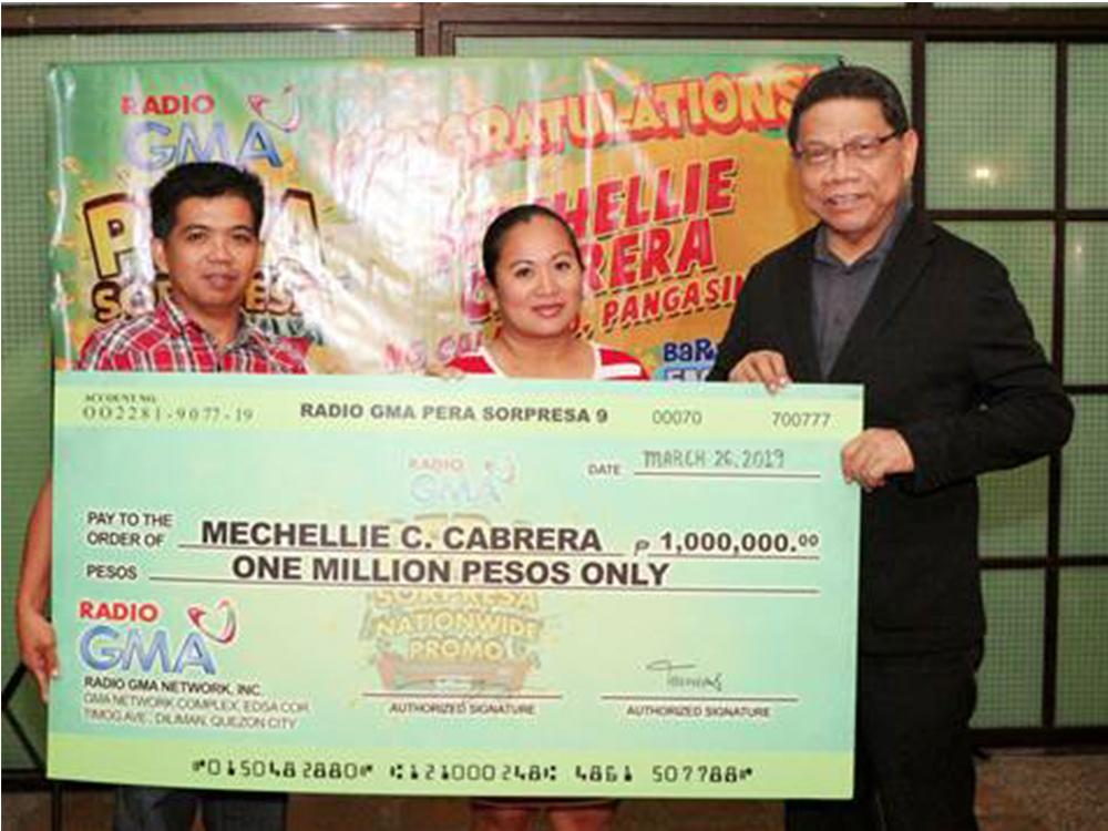 (Right to left) RGMA President Mike Enriquez awards the Pera Sorpresa 9 grand prize to Mechellie Cabrera and her husband Renato.